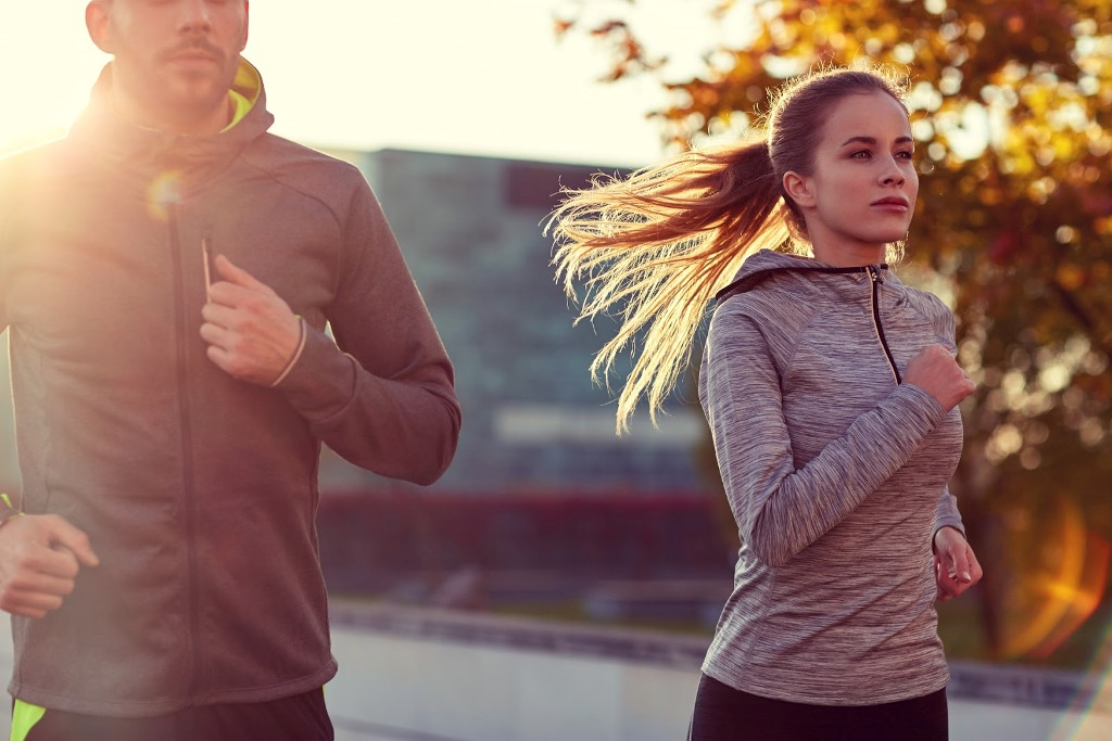 fitness, sport, people and lifestyle concept – couple running outdoors